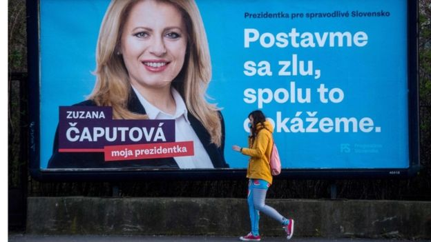 "A girl walks past one of Ms Caputova's campaign posters, which reads ""Stand up against evil, together we can do it""."