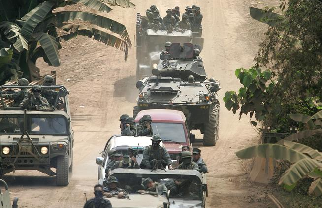 "FILE - In this Saturday, March 3, 2007 file photo, a convoy of Filipino and U.S. troops negotiate a dirt road as they secure an area where the closing ceremonies of the annual military exercise called ""Balikatan,"" or ""shouldering the load together,"" are being held at the coastal village of Bato-Bato in Indanan town, Jolo province, southern Philippines. After more than a decade of helping fight al-Qaida-linked militants, the United States is disbanding an anti-terror contingent of hundreds of elite American troops in the southern Philippines where armed groups such as Abu Sayyaf have largely been crippled, officials said Thursday, June 26, 2014. (AP Photo/Aaron Favila)"