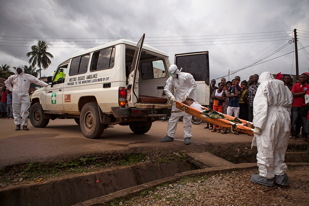 "In this photo taken on Wednesday, Sept. 24, 2014, healthcare workers load a man suspected of suffering from the Ebola virus onto an ambulance in Kenema, Sierra Leone, Thursday, Sept. 25, 2014.  Sierra Leone restricted travel Thursday, Sept. 25, 2014 in three more ""hotspots"" of Ebola where more than 1 million people live, meaning about a third of the country's population is now under quarantine. Sierra Leone is one of the hardest hit countries in the Ebola outbreak sweeping West Africa that is believed to have killed more than 2,900 people, according to World Health Organization tolls published Thursday. (AP Photo/ Tanya Bindra)"